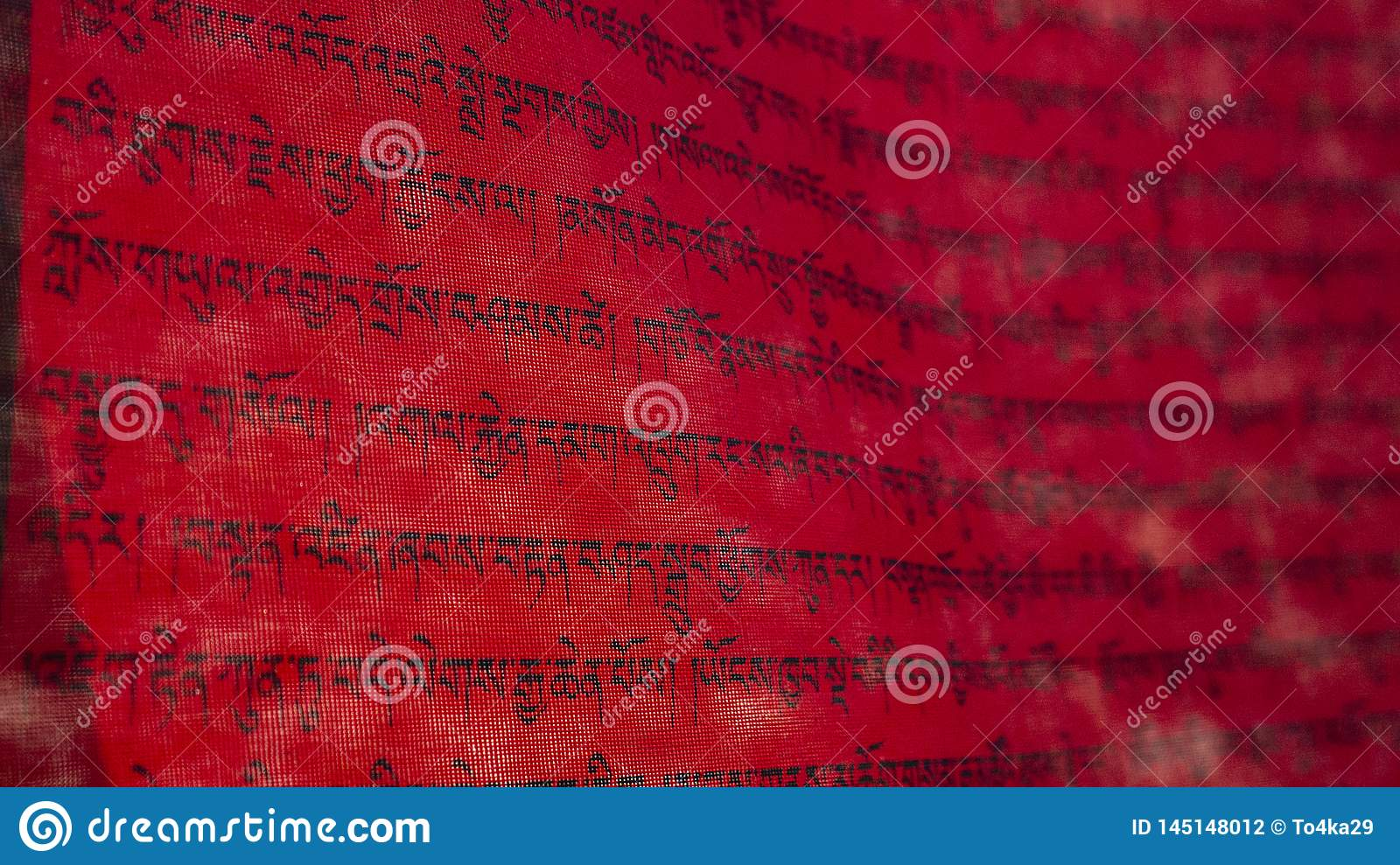 Tibetan letters on red textile. Mantra. Calligraphy