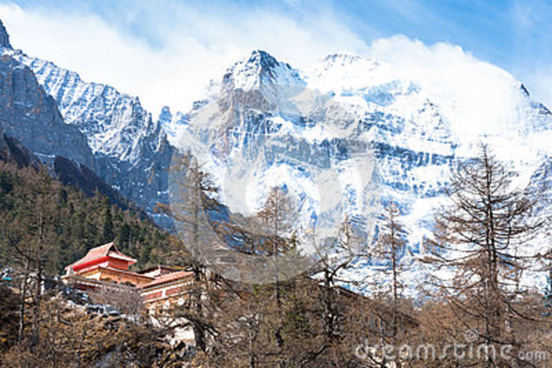 Tibetan temple on the snow mountain with gray rocks in Yading Nature Reserve,