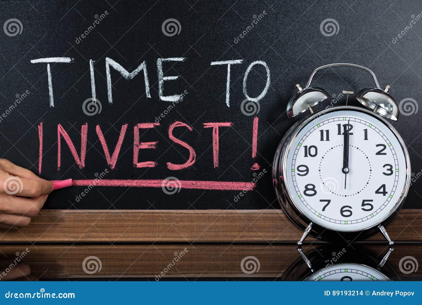Tid som investerar begreppet som är skriftligt på svart tavla