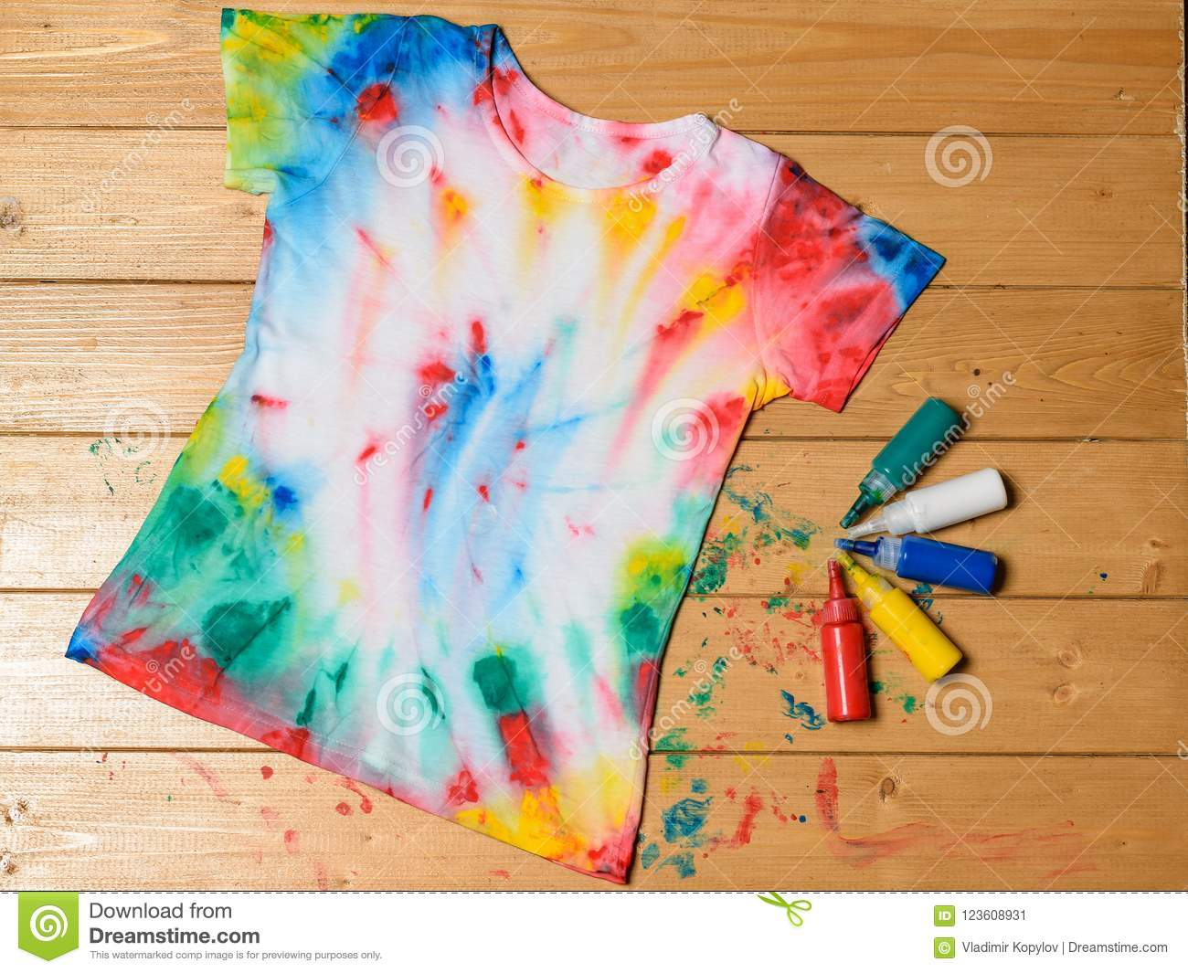 33c4e8b4 Tie dye style t-shirt and six cans of fabric paint on wooden rustic table