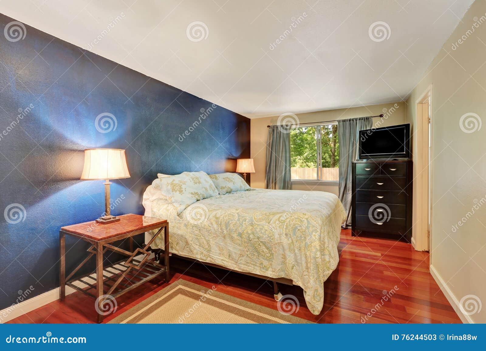tiefe blaue kontrastwand im schlafzimmer mit hölzernem bodenbelag