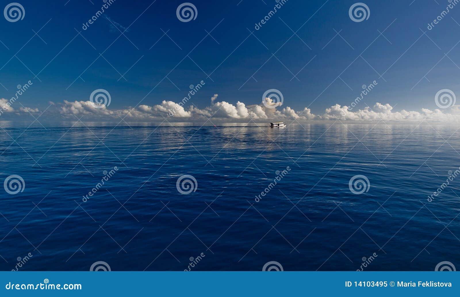 Tiefer blauer Ozean und weiße Wolken