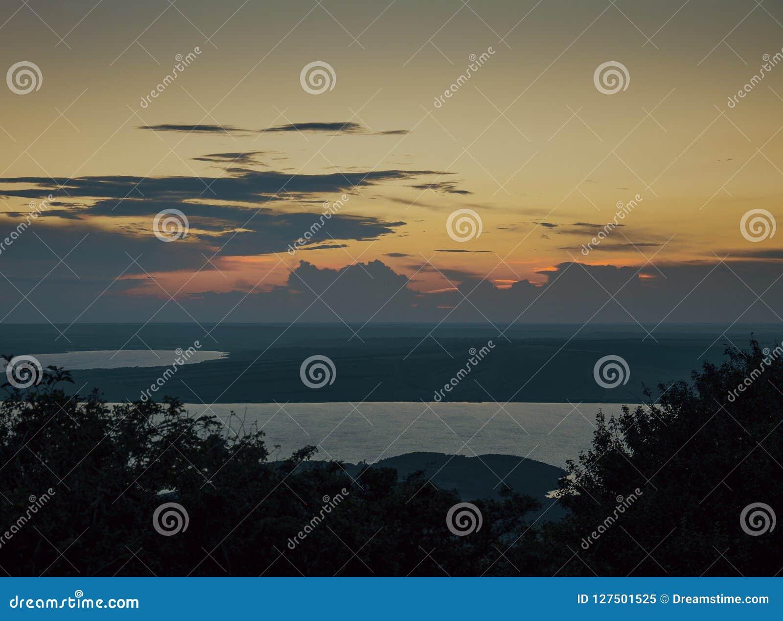 Tiempo de la tarde de la altura de las montañas sobre el lago