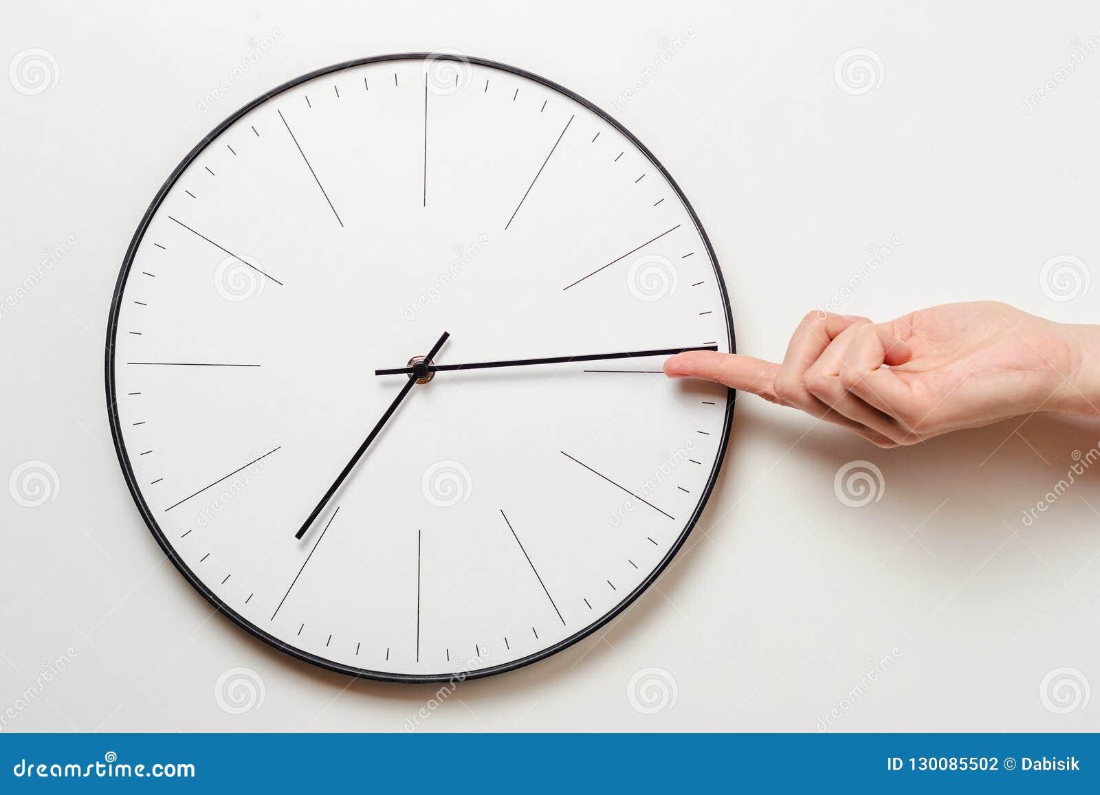 Tiempo de parada de la mano de la mujer en el reloj redondo, el finger femenino retira la flecha minuciosa del reloj, de la gesti