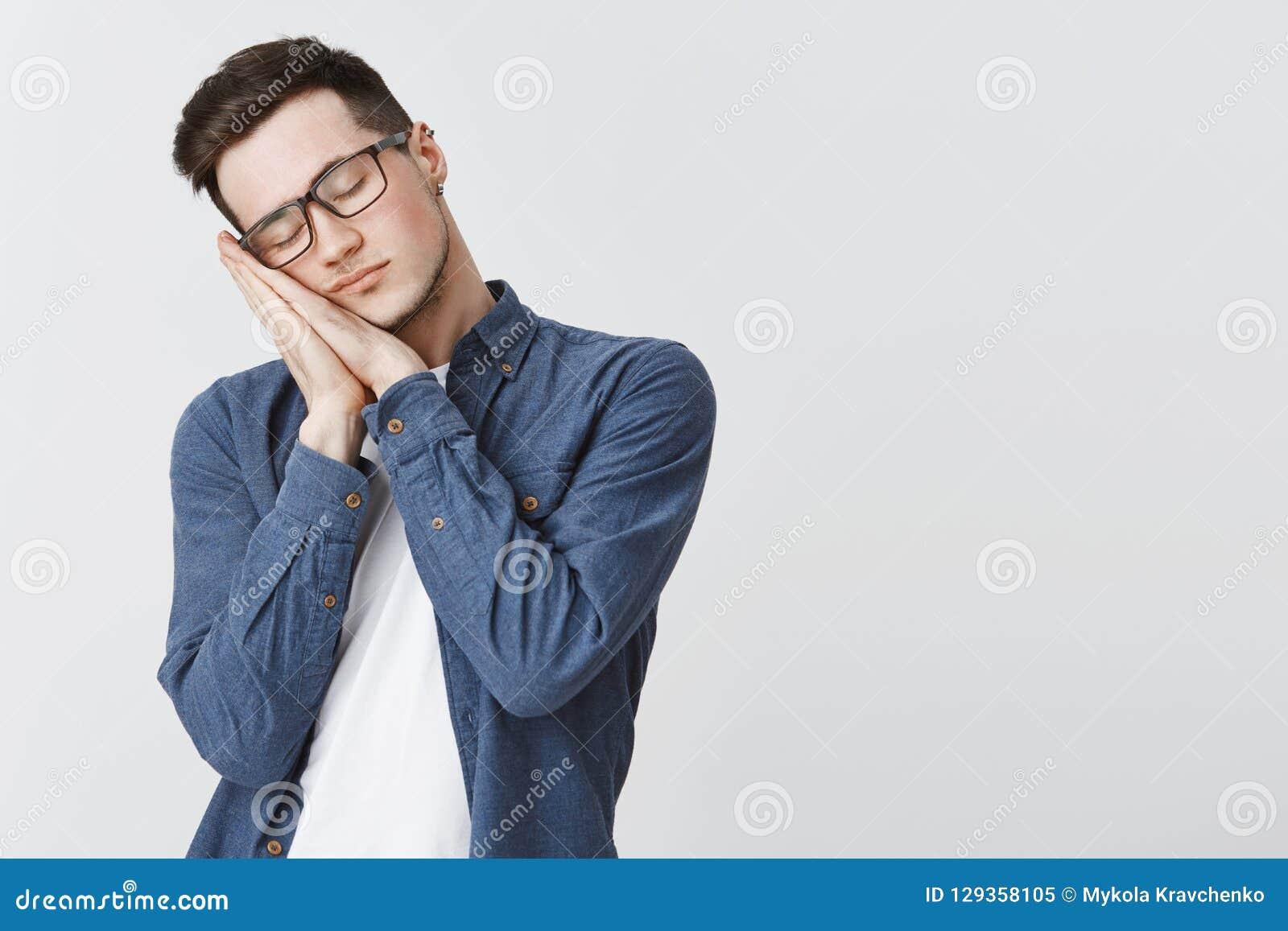 Tiempo de sueño Hombre joven atractivo cansado con el oído perforado y los vidrios que se colocan con los ojos cerrados que se in