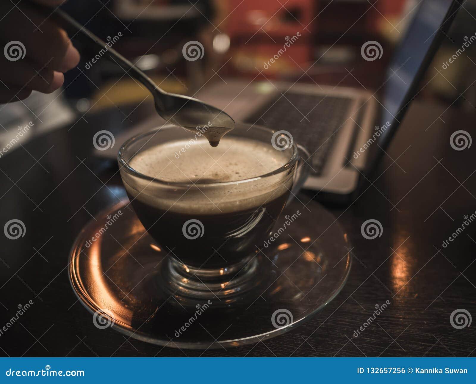 Tiempo del descanso para tomar café con el ordenador portátil en la tabla de madera en cafetería Re