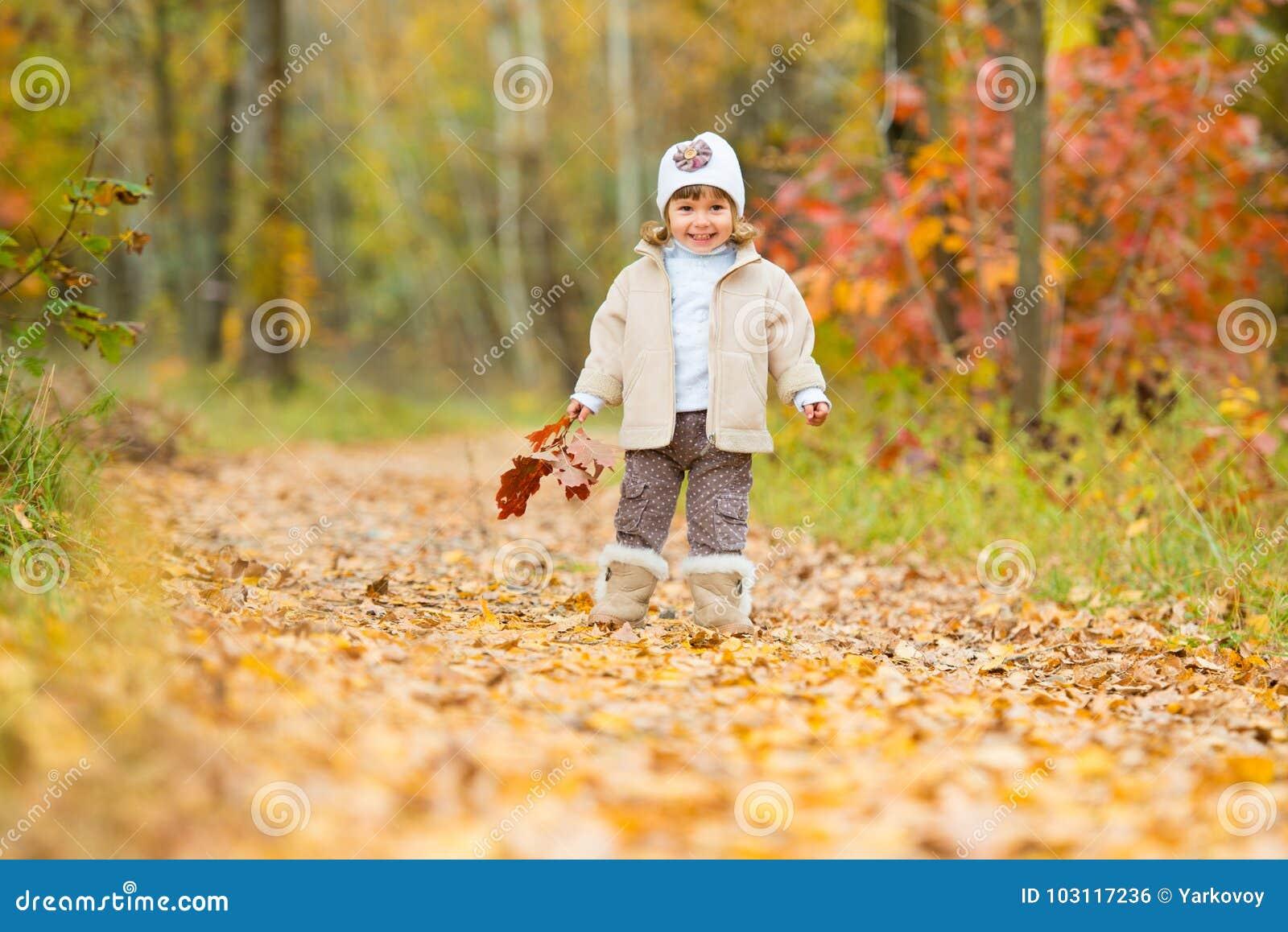 Tiempo del otoño, pequeño bebé feliz, la muchacha camina a lo largo de la trayectoria con un ramo de hojas de otoño
