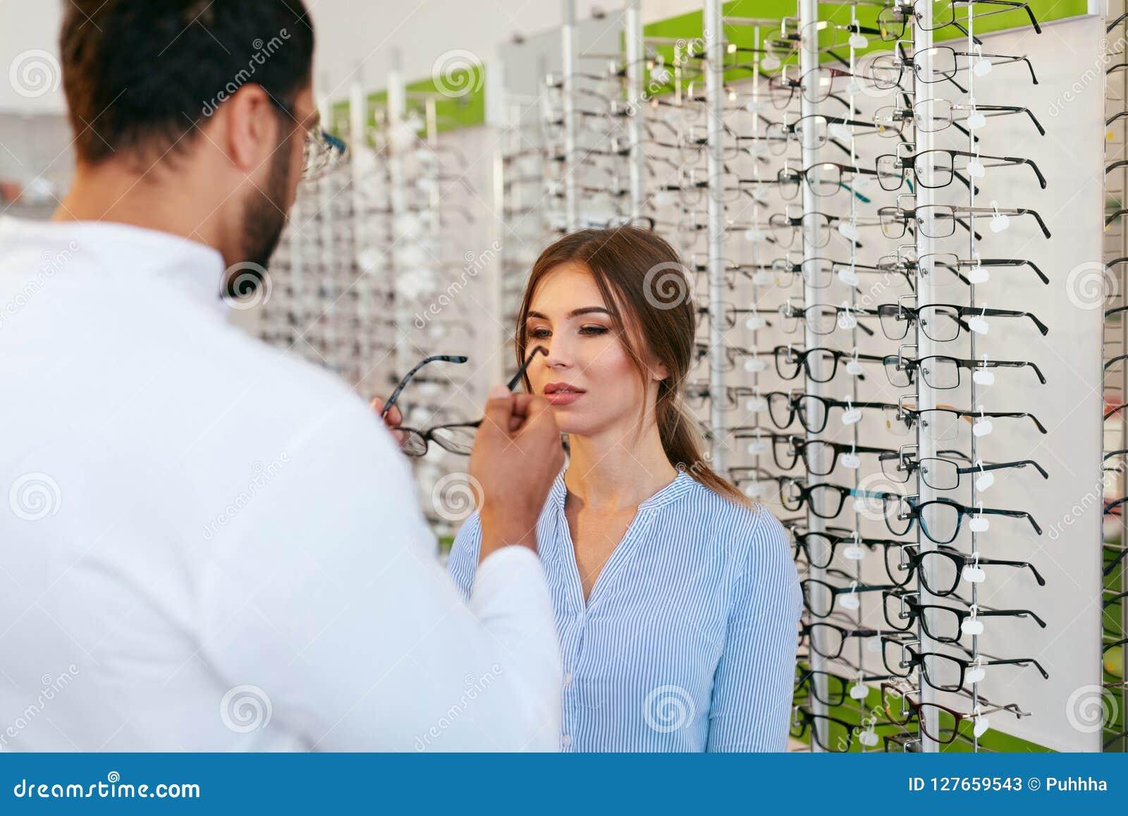 Tienda óptica Lentes de Helping Woman Choosing del oculista
