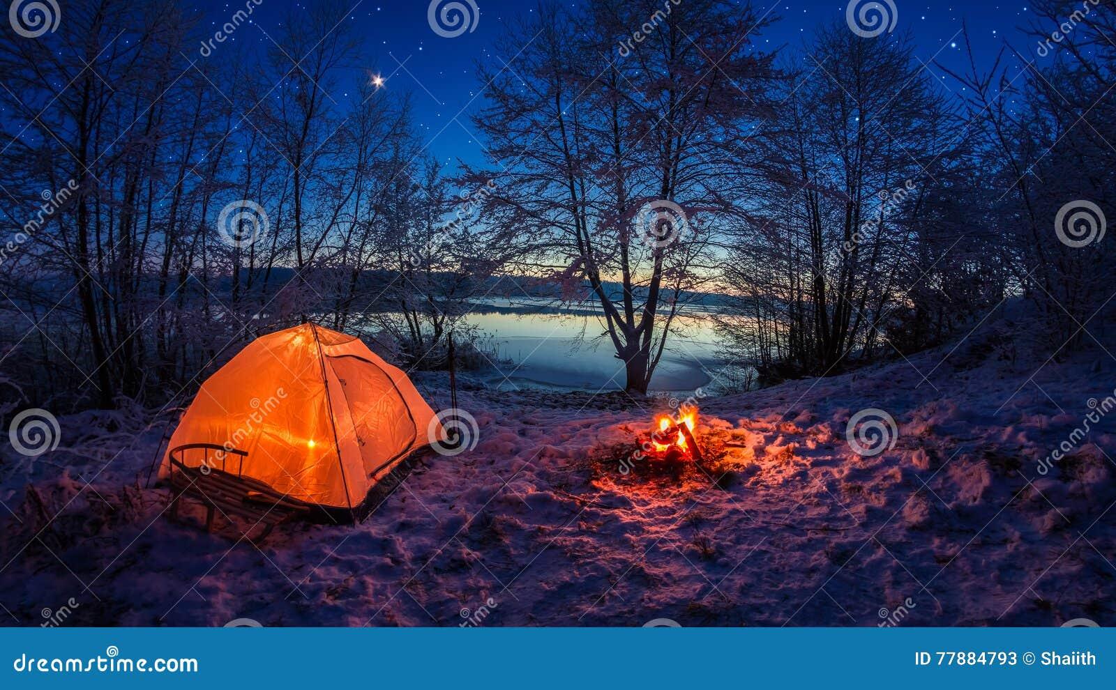 Tienda Iluminada En El Campo Del Invierno Por El Lago En La Noche Con Las Estrellas Foto de archivo