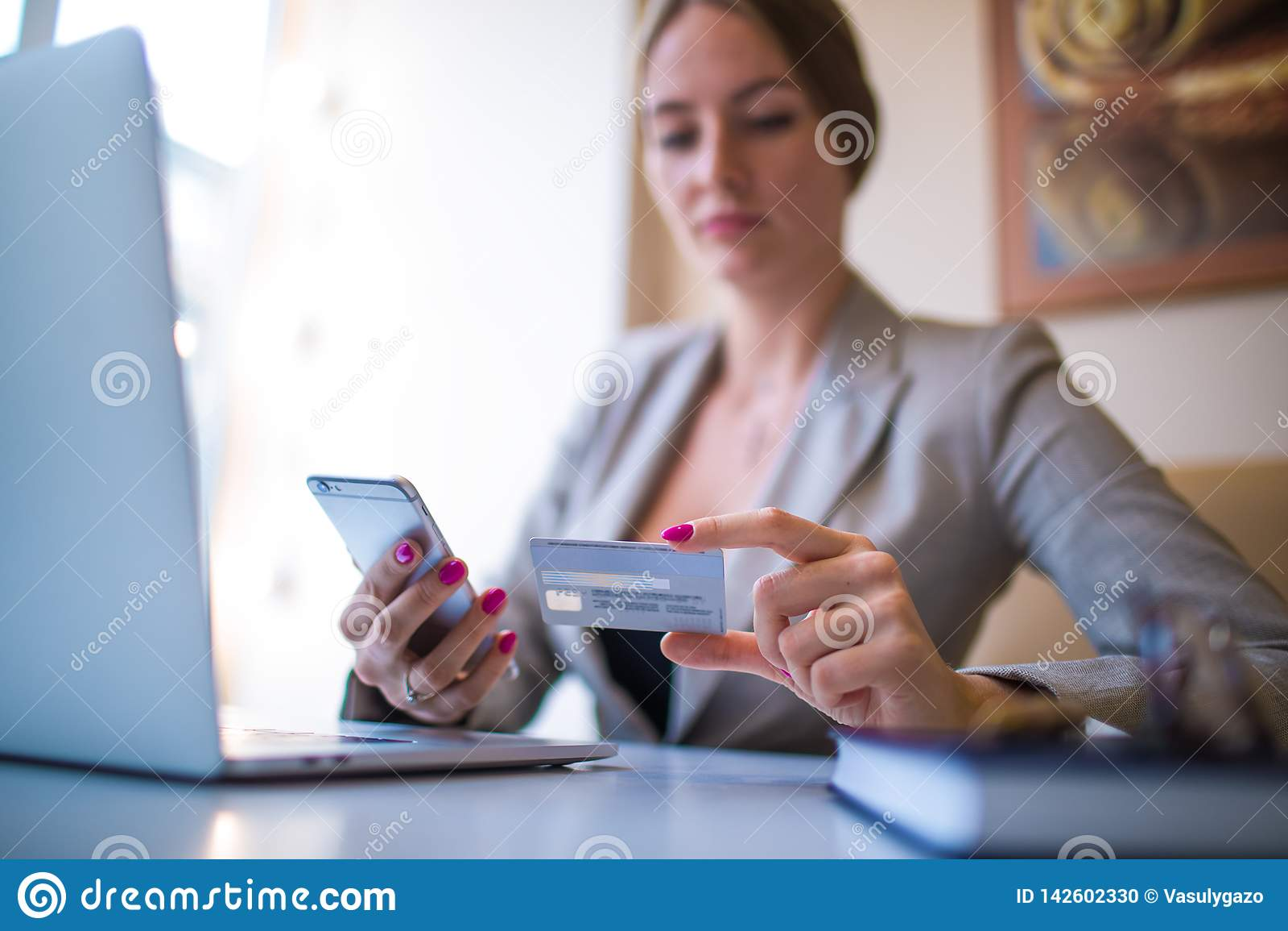 Tienda que hace compras en línea de fabricación femenina vía el artilugio del teléfono móvil