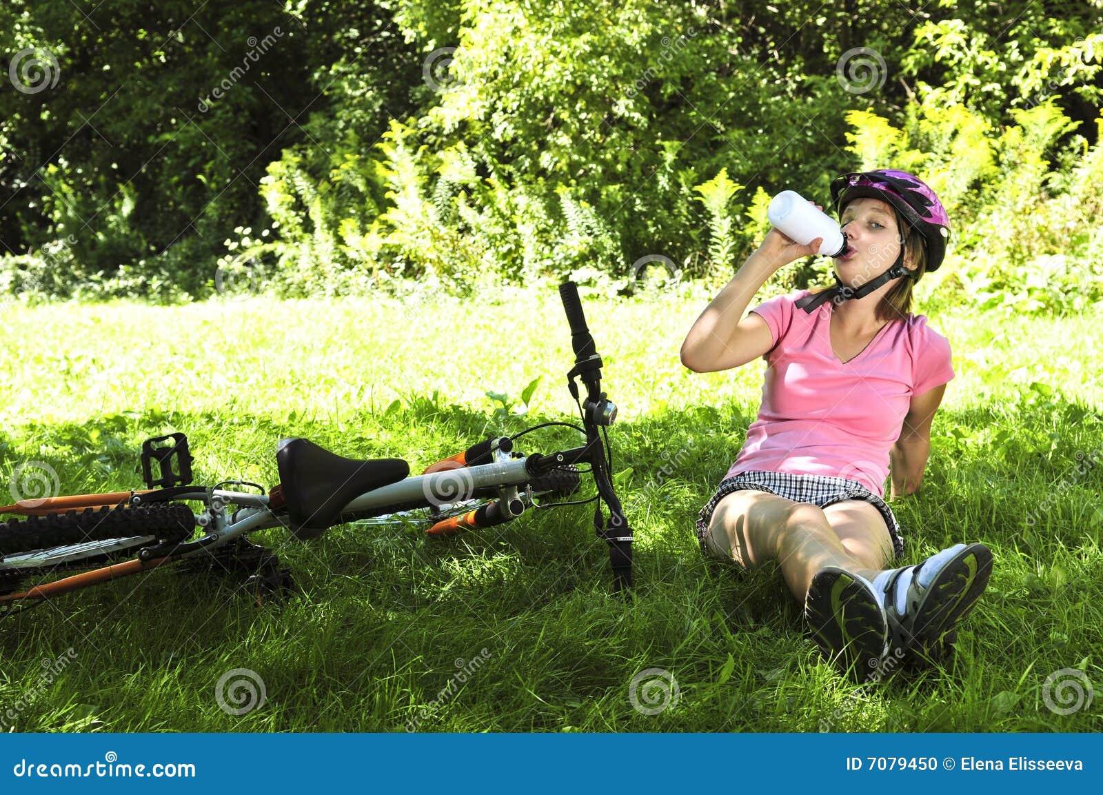 Tiener die in een park met een fiets rust