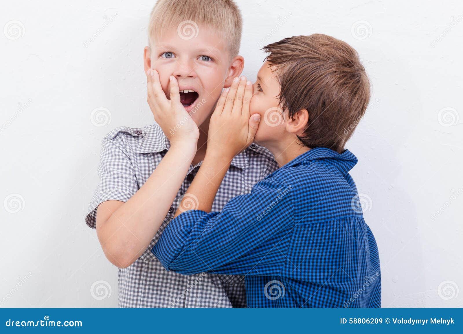Tiener die in het oor een geheim fluisteren aan