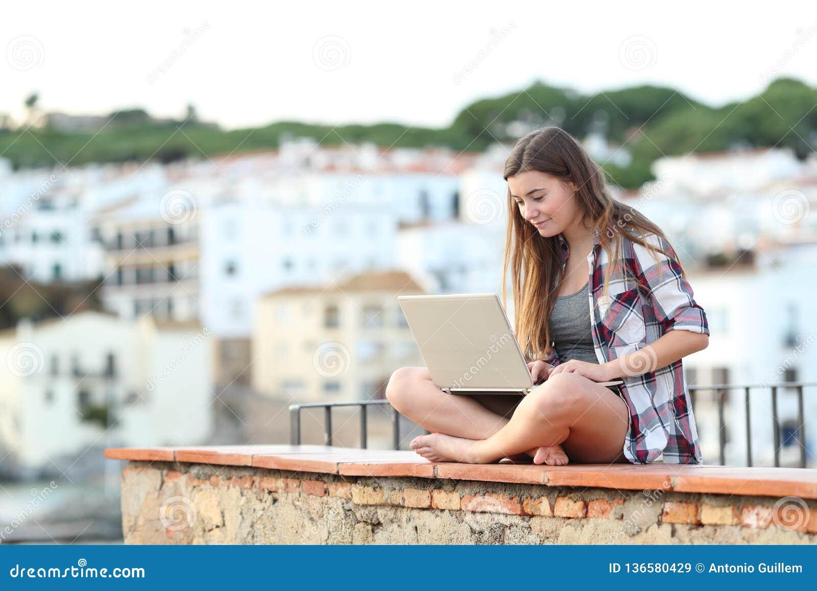 Tiener die laptop op een richel in een stad met behulp van