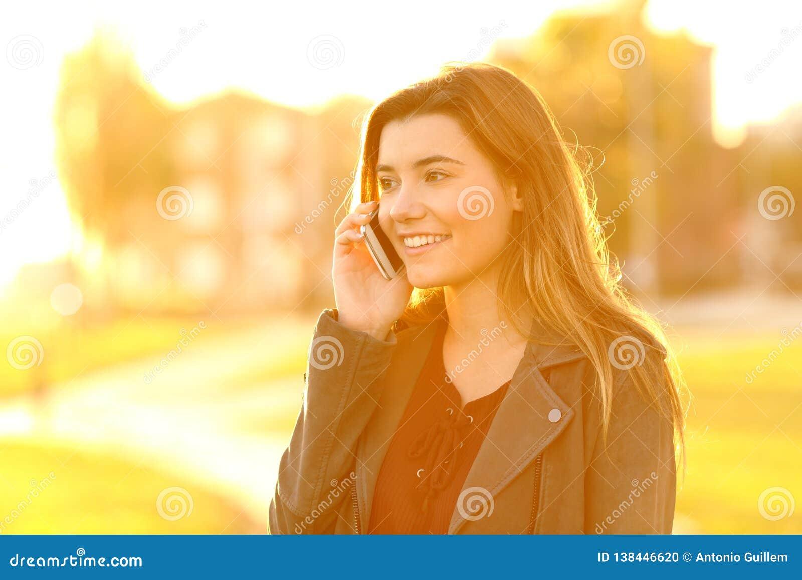 Tiener die op telefoon bij zonsondergang spreken