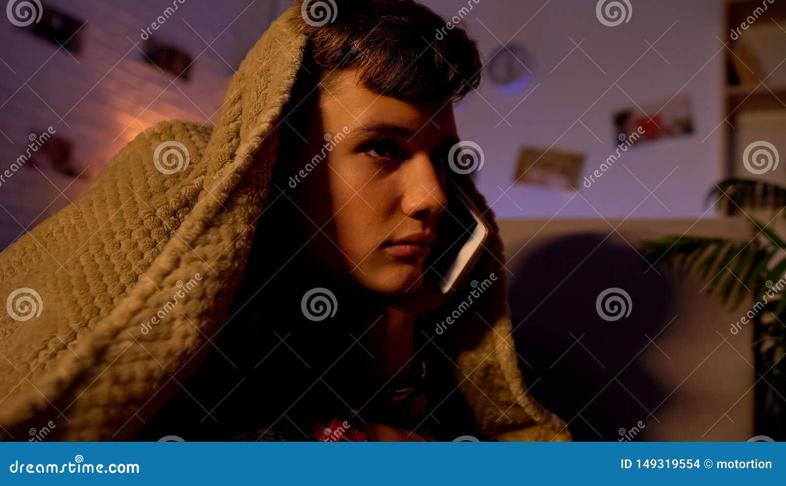 Tiener die op telefoon tot laat spreken - nacht, die onder deken, mededeling liggen