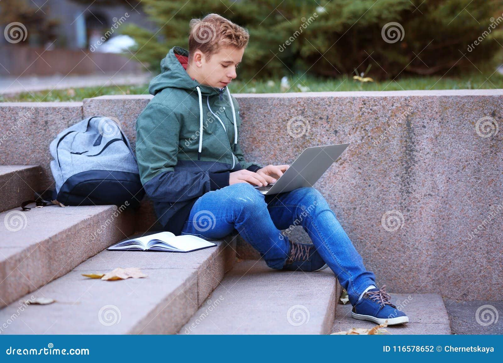 Tiener met laptop zitting op stappen