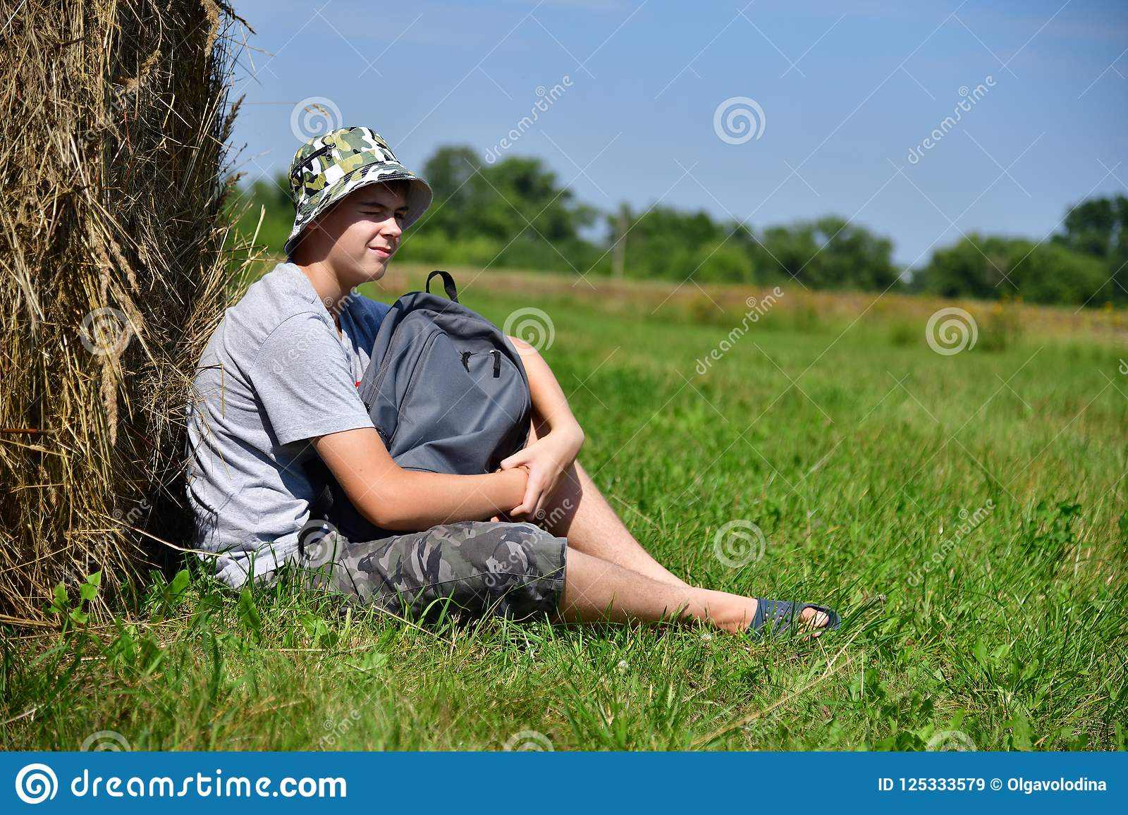Tiener met rugzakzitting naast stapel van stro