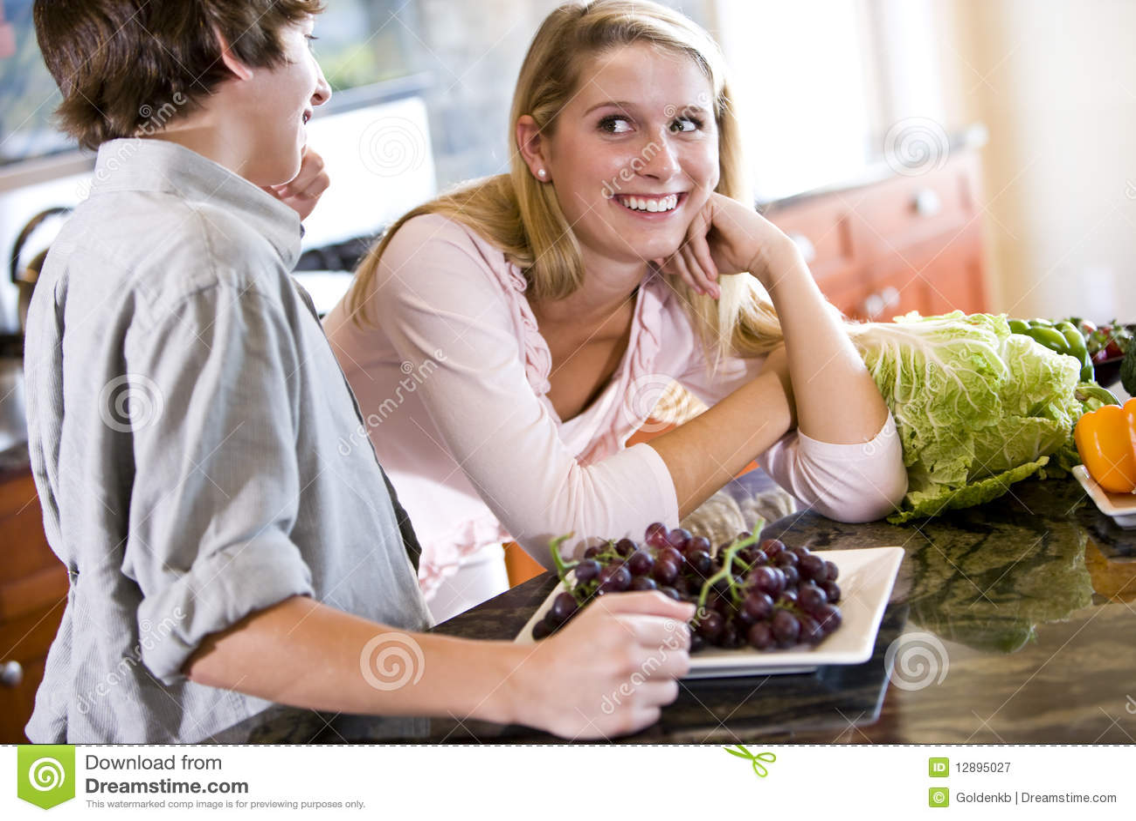 Tiener op keukenteller met broer