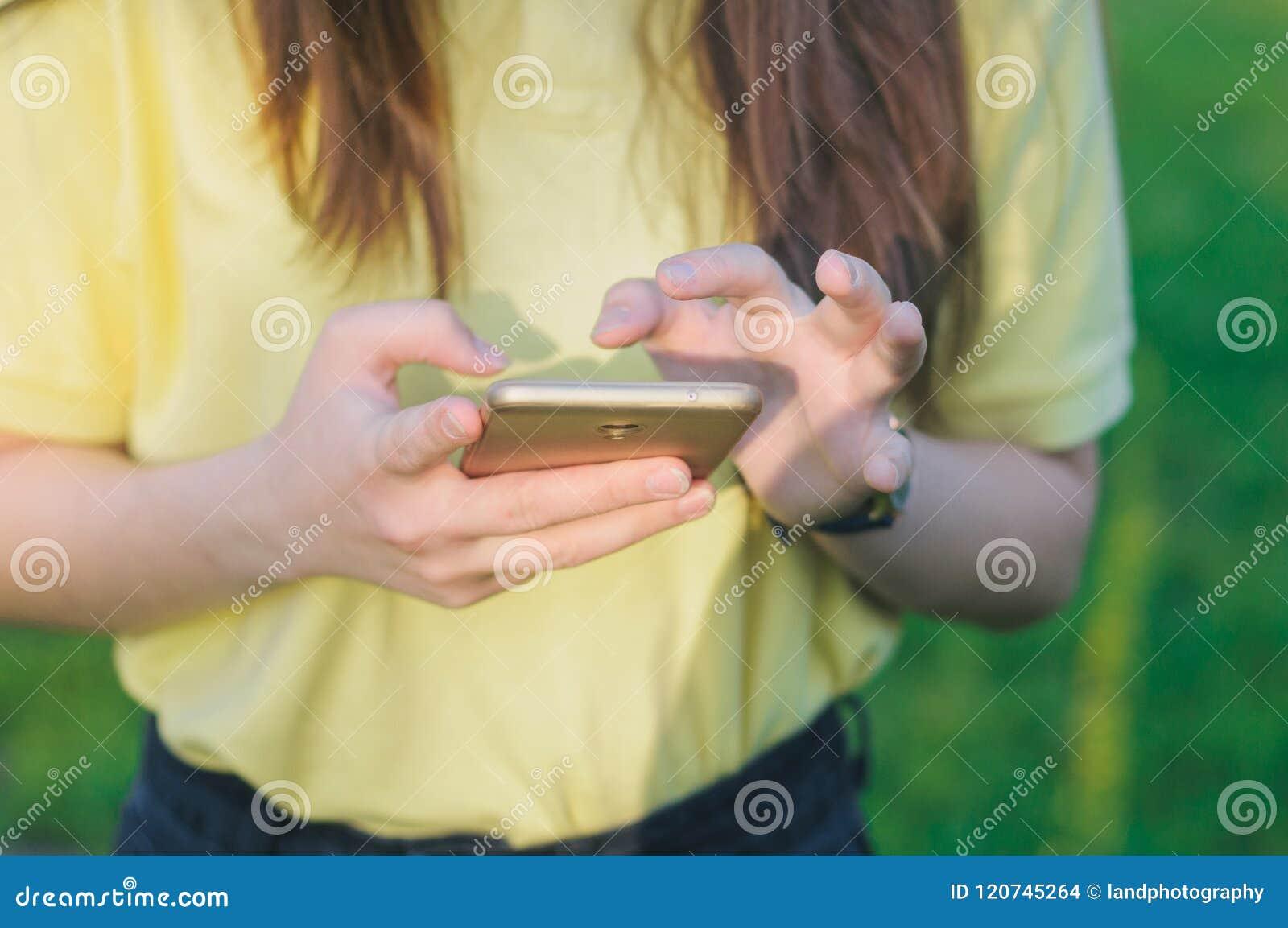 Tiener wat betreft het scherm Vrouw die een mobiele telefoon in handen houden
