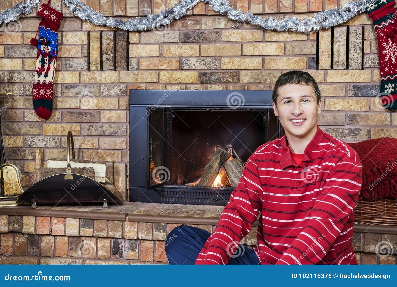 Tienerjongen het glimlachen zitting voor comfortabele open haard verfraaide FO