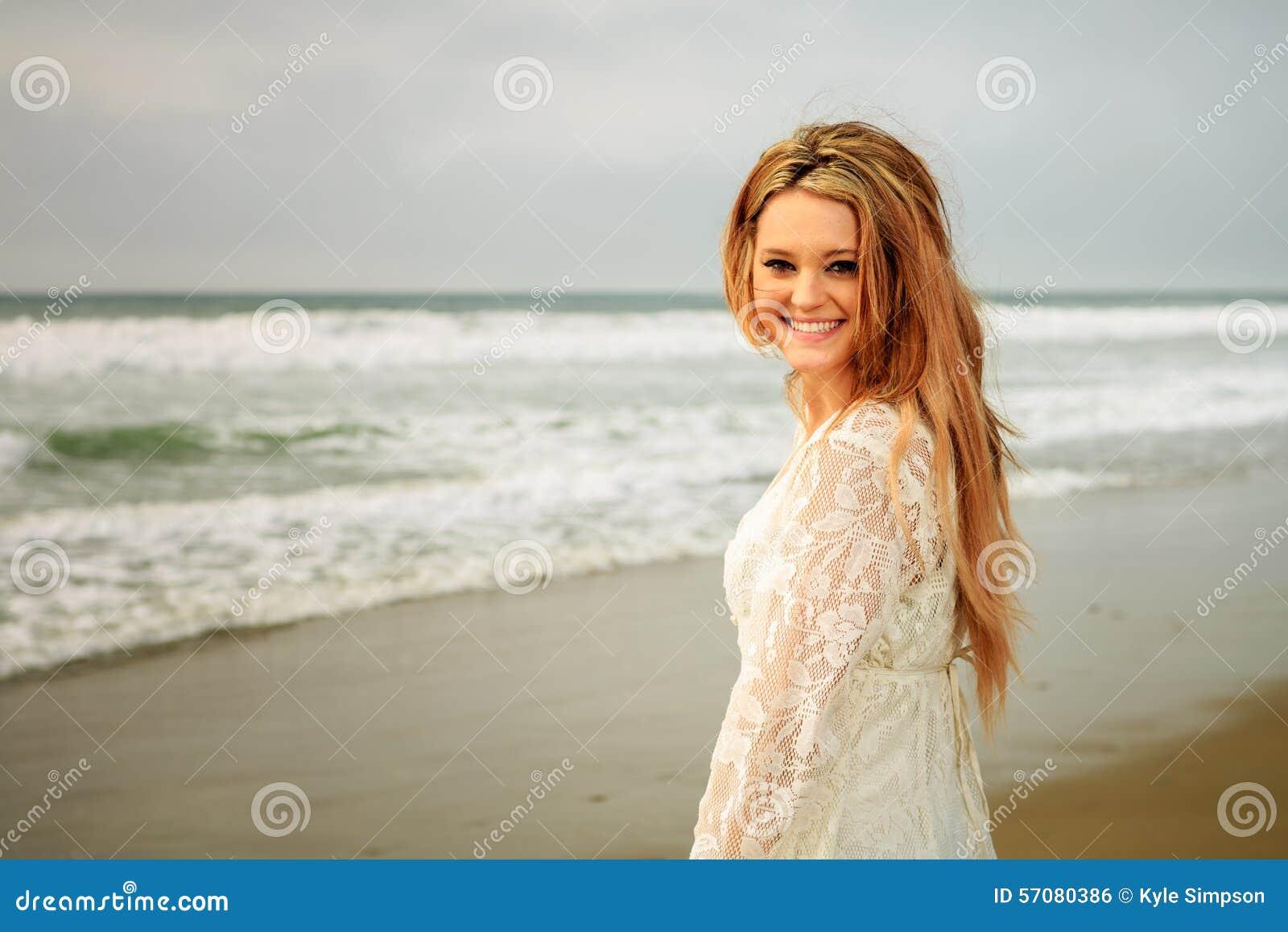 Tienermeisje bij het strand door de golven