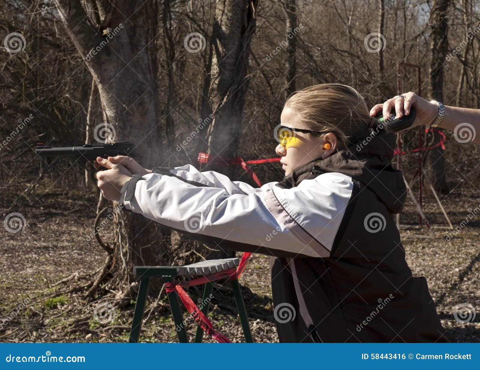 Tienermeisje die pistool met de handtiming van de bus schieten