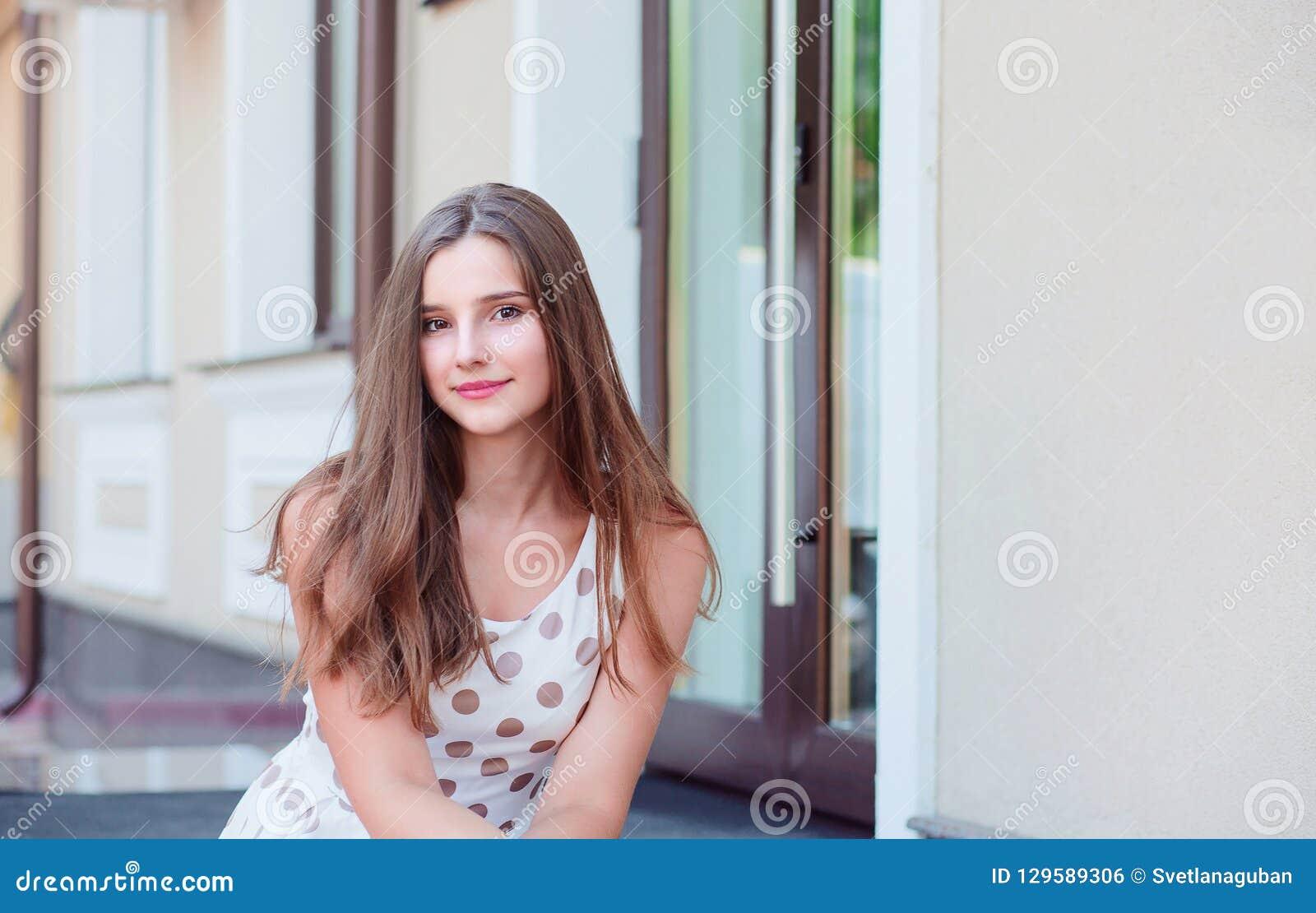 Tienermeisje met lange donkerbruine haarzitting op de marmeren stappen