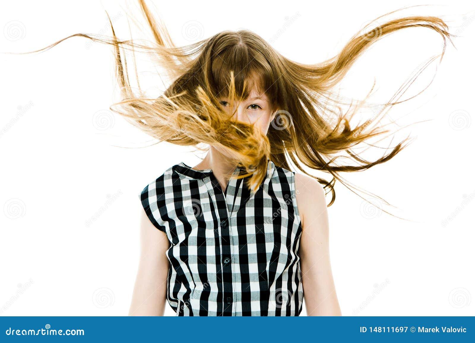 Tienermeisje met lange rechte vliegende haren die haar oog behandelen