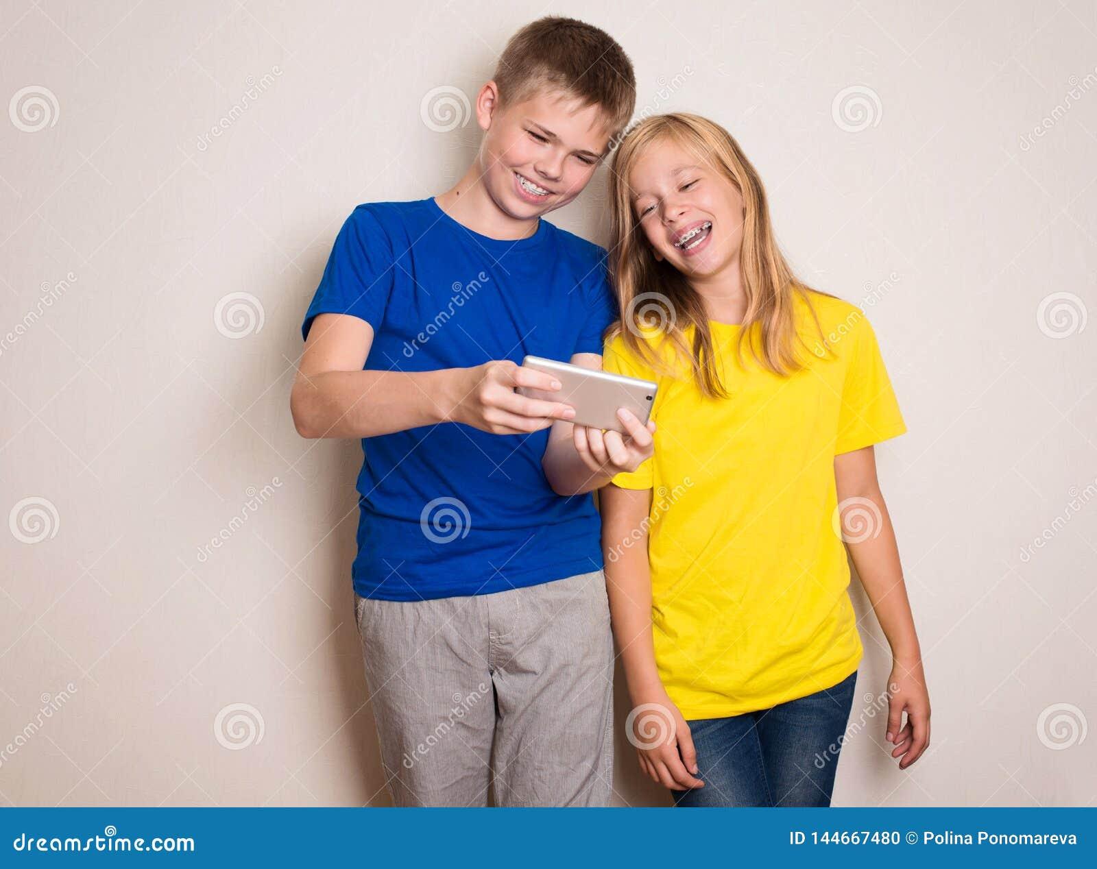 Tieners die pret met mobiele telefoons hebben Modern levensstijl en technologieconcept Kinderen die op foto of video op letten