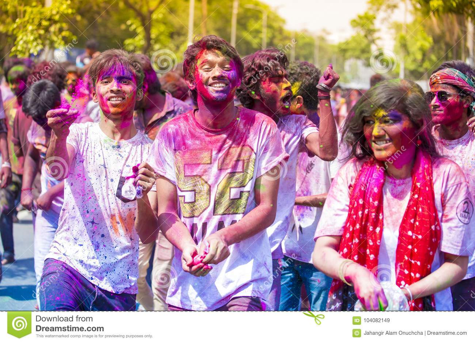 Tieners en kinderen die pret met gekleurd water en holipoeder hebben tijdens het Hindoese festival van kleuren, Dhaka, Bangladesh
