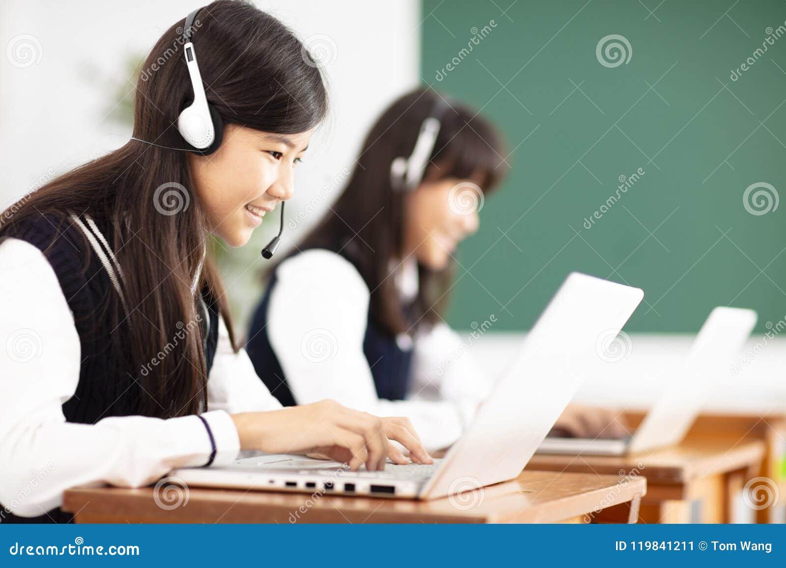 Tienerstudent die online met hoofdtelefoons en laptop leren
