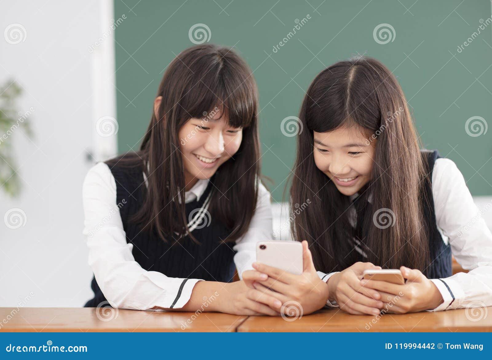 Tienerstudente die op de slimme telefoon in klaslokaal letten