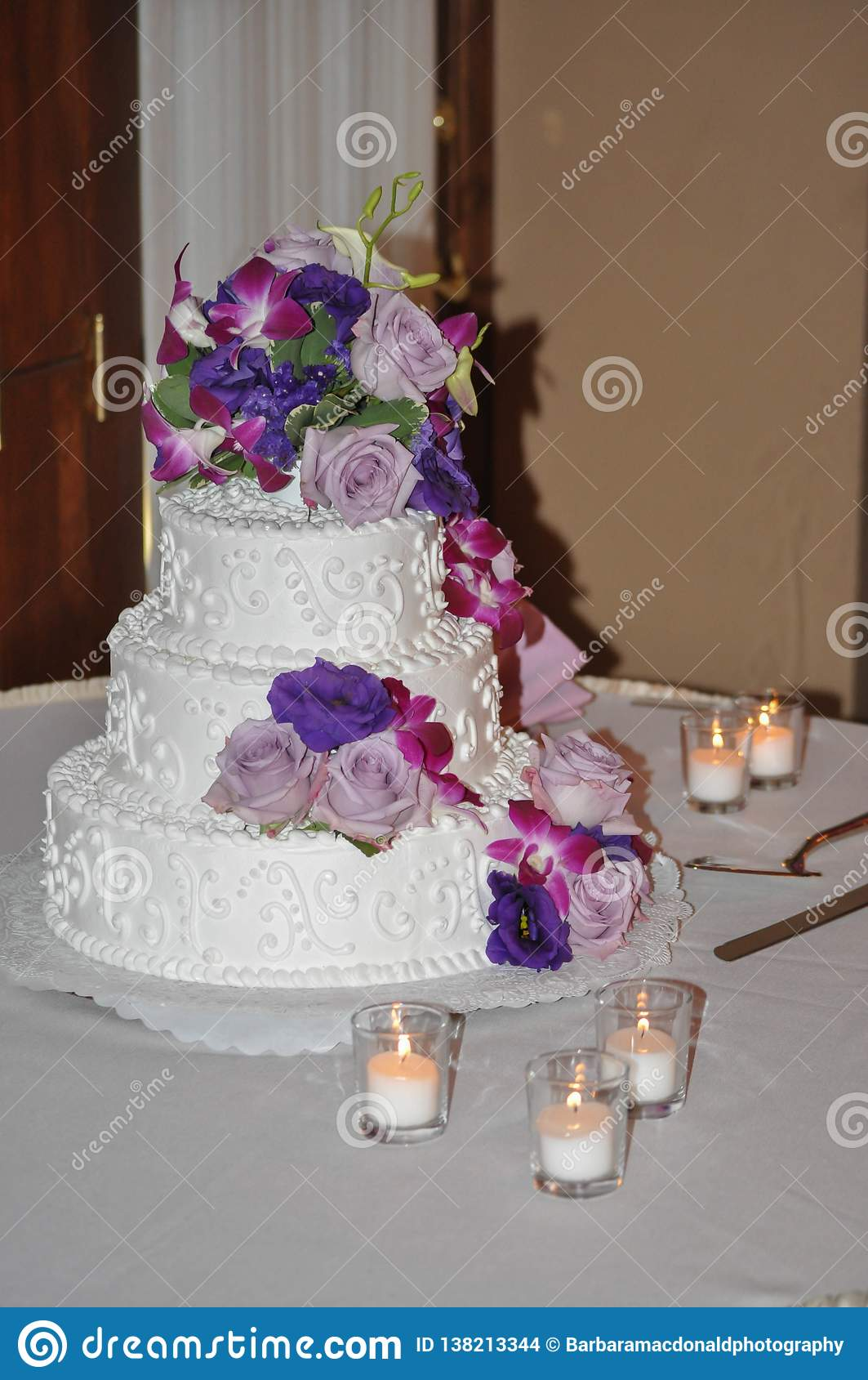 Tiered bröllopstårta med stearinljus, rosor och blommor