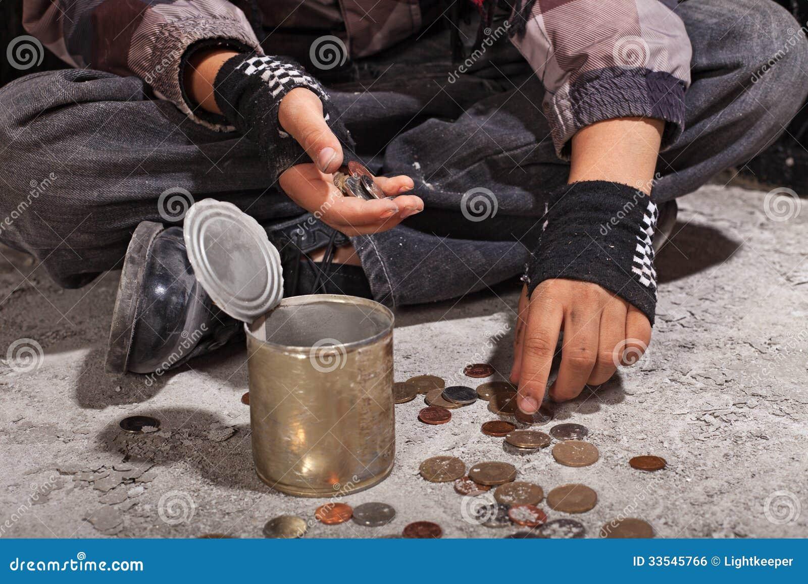 Tiggarebarn som räknar mynt som sitter på skadat konkret golv