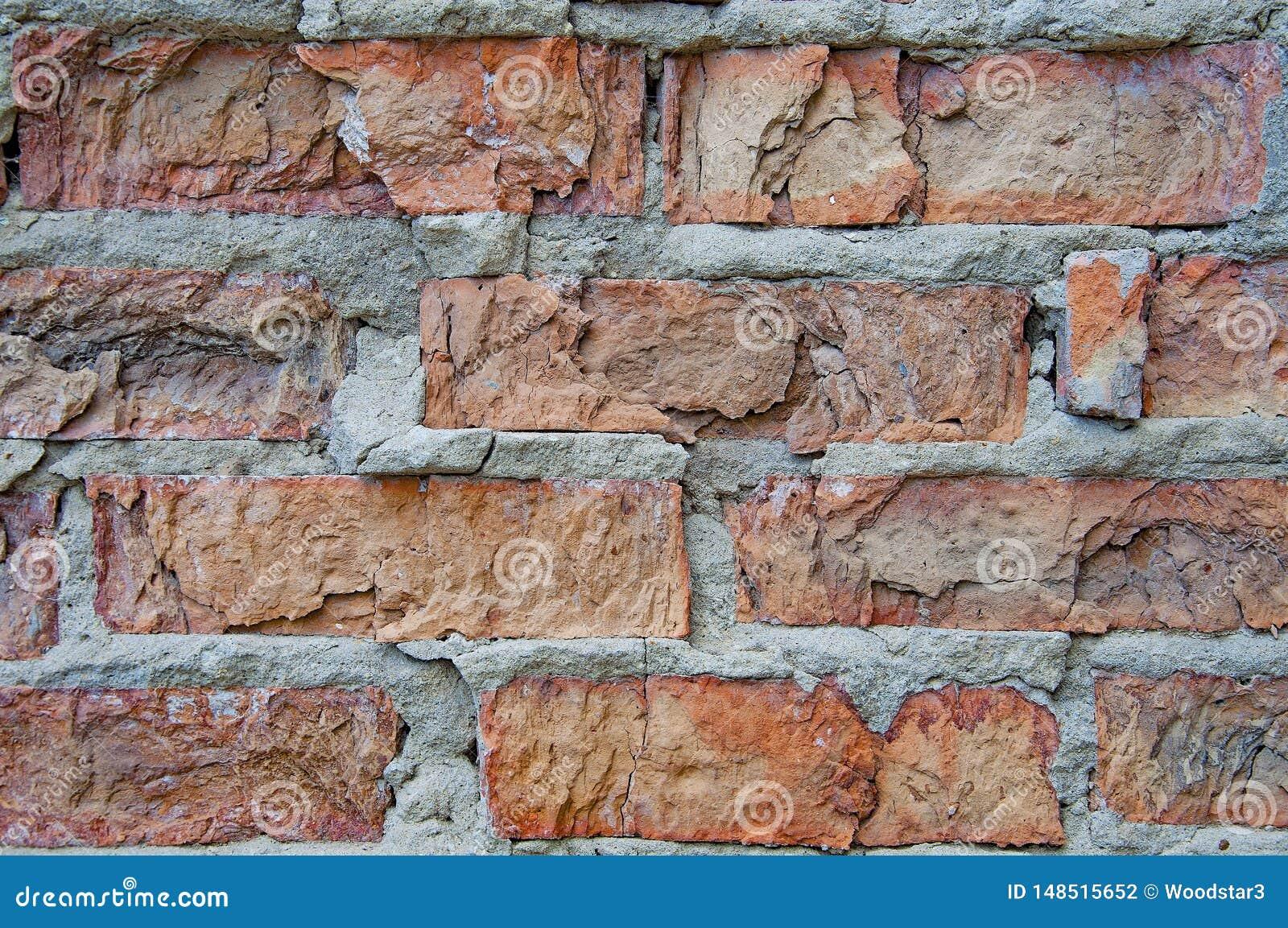 Tijolos fundo e texturas na parede Quebras pobres do tijolo Dano das r?guas