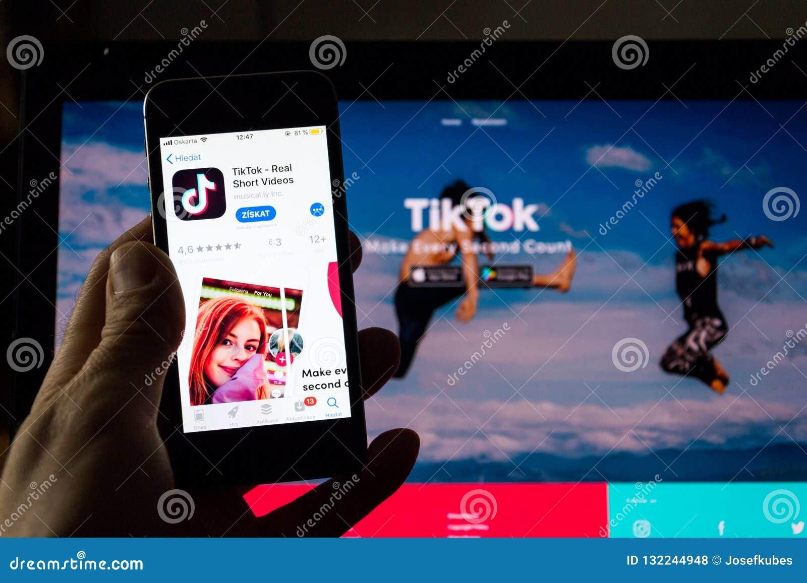 TikTok mobiel video-deelt app bedrijfembleem op het telefoonscherm met Internet-homepage op achtergrond
