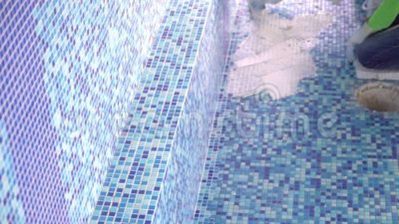 Tile grouting in swimming pool.