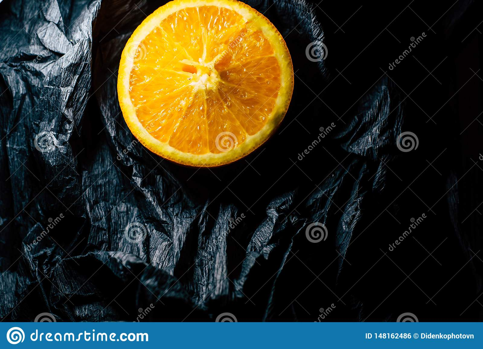 Till h?lften en apelsin p? en m?rk bakgrund