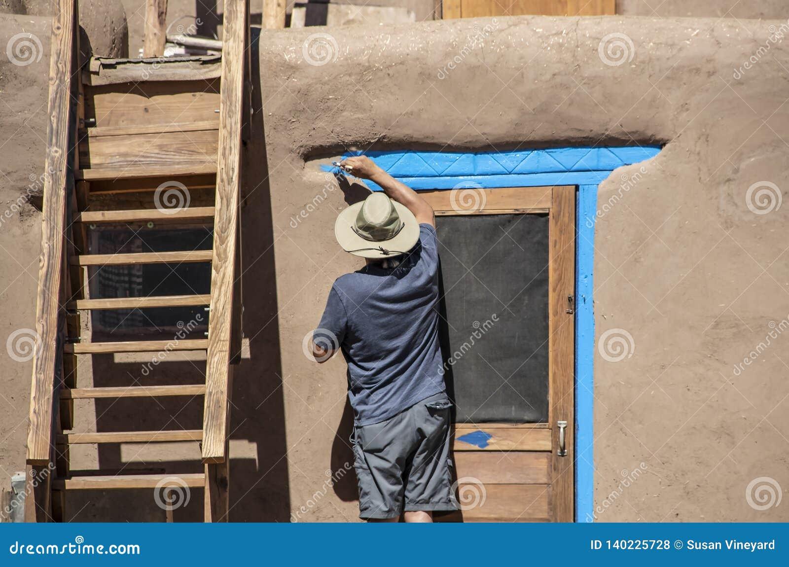 Tillbaka av indianmannen i kortslutningar och denskjorta och solhatten som målar ljus blått-turkos runt om dörren av en gyttjaAdo