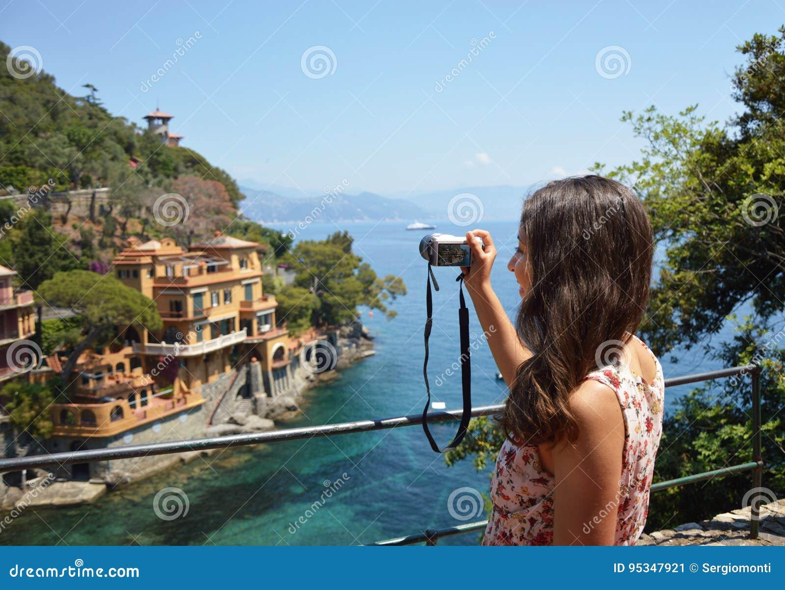Tillbaka sida av den unga kvinnan som tar bilden av den härliga italienska fjärden i Portofino, lyckligt lopp till Europa, begrep