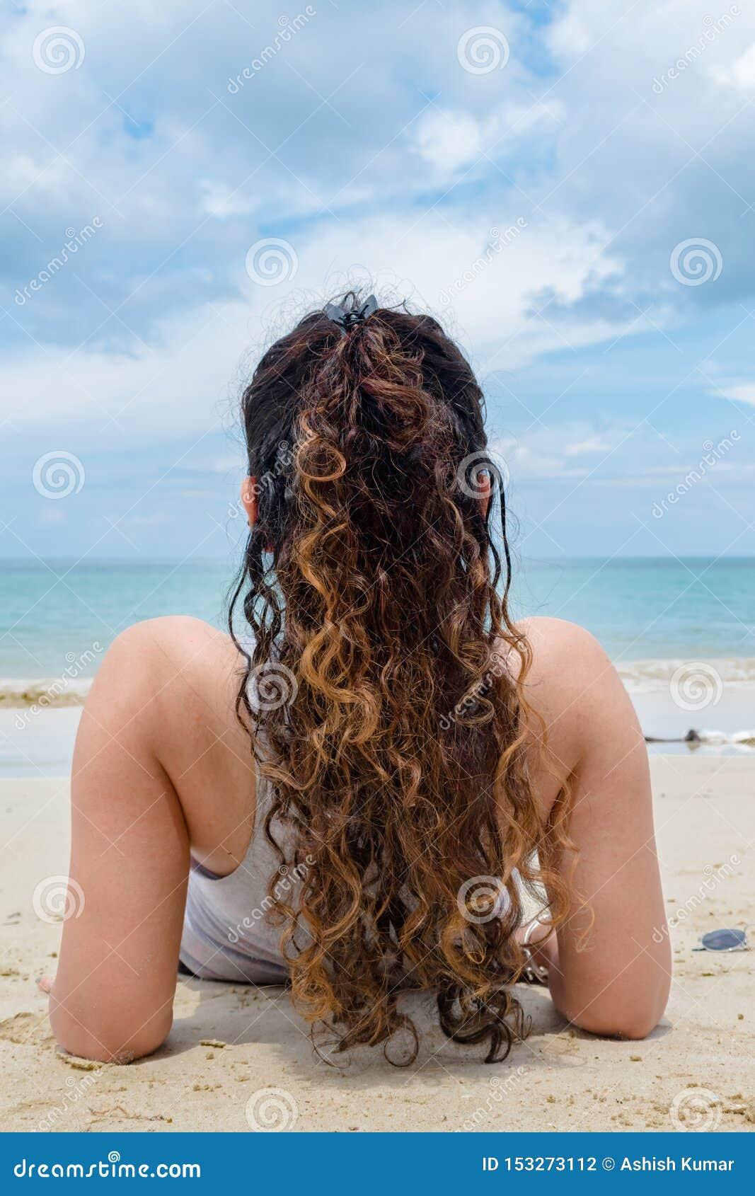 Tillbaka sikt av den ganska flådde flickan och att ha lockiga hår av guld- färg, solo koppla av & solbada på stranden på den exot