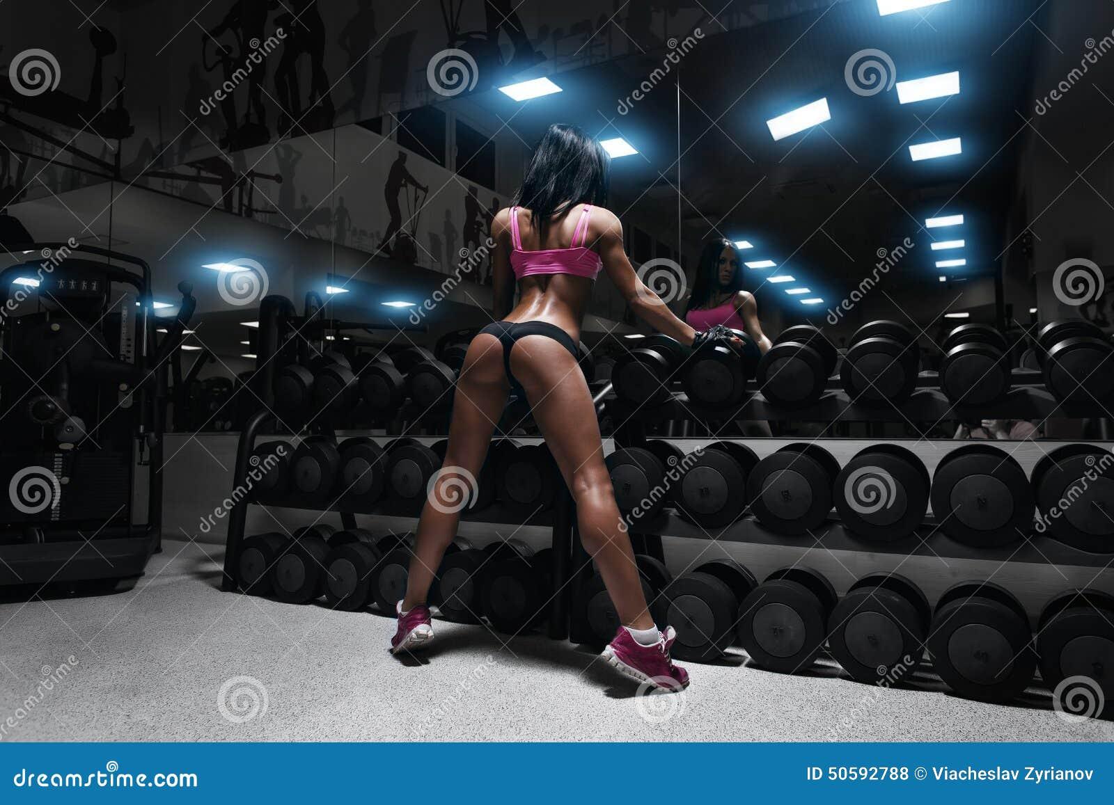 Tillbaka sikt av den sexiga unga brunettkvinnan som vilar i idrottshallen