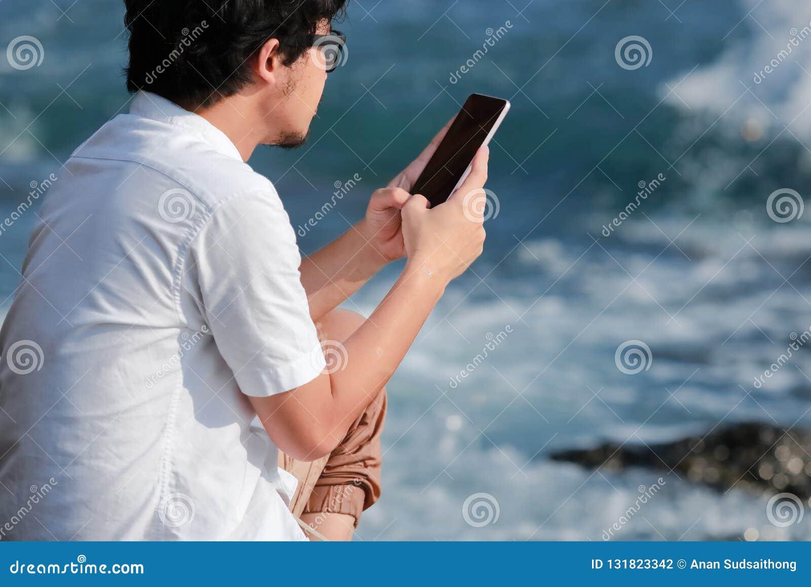 Tillbaka sikt av den unga asiatiska mannen som använder den mobila smarta telefonen på havskusten Internet av sakerbegreppet