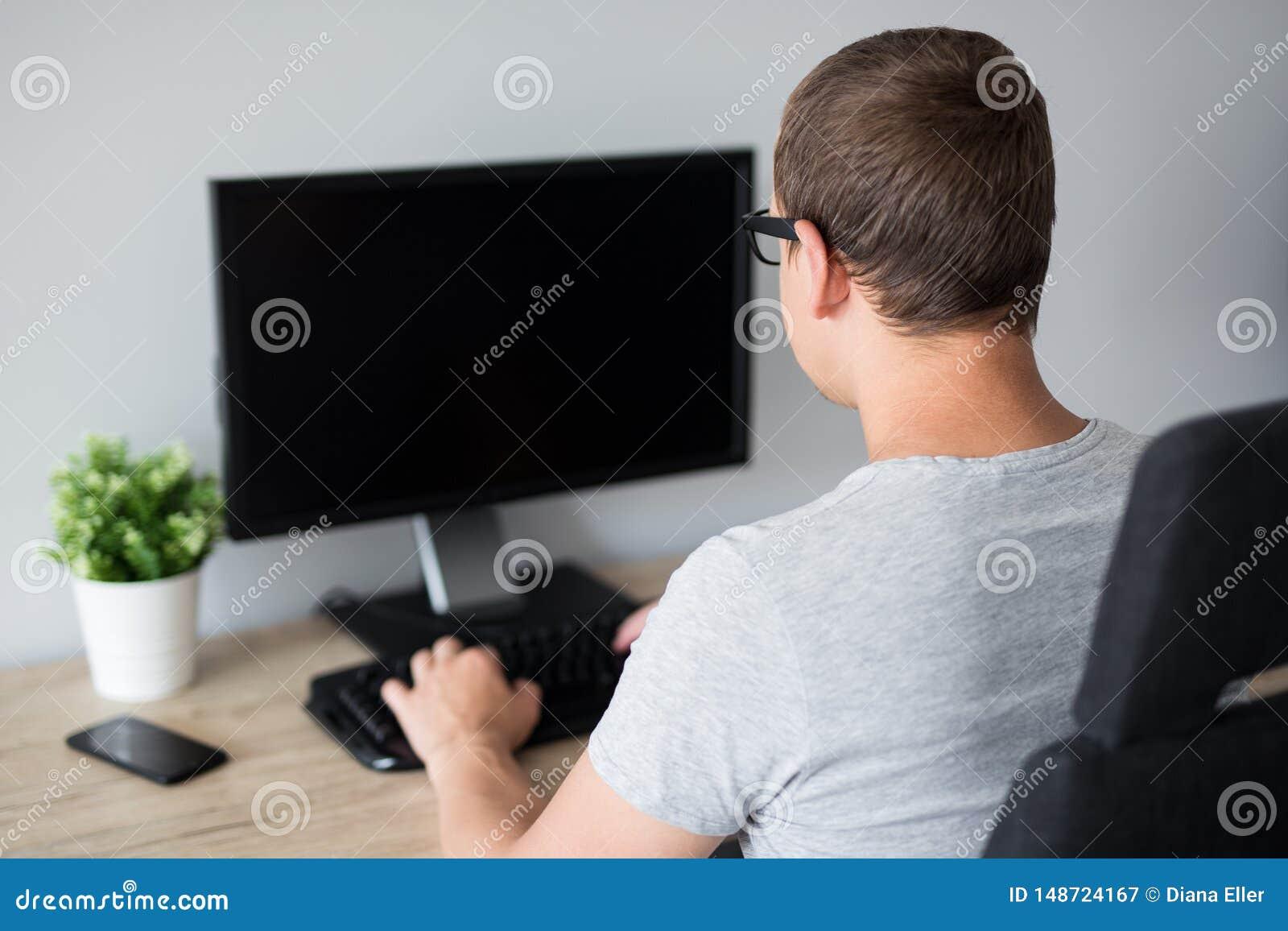 Tillbaka sikt av den unga mannen som anv?nder datoren med den tomma sk?rmen