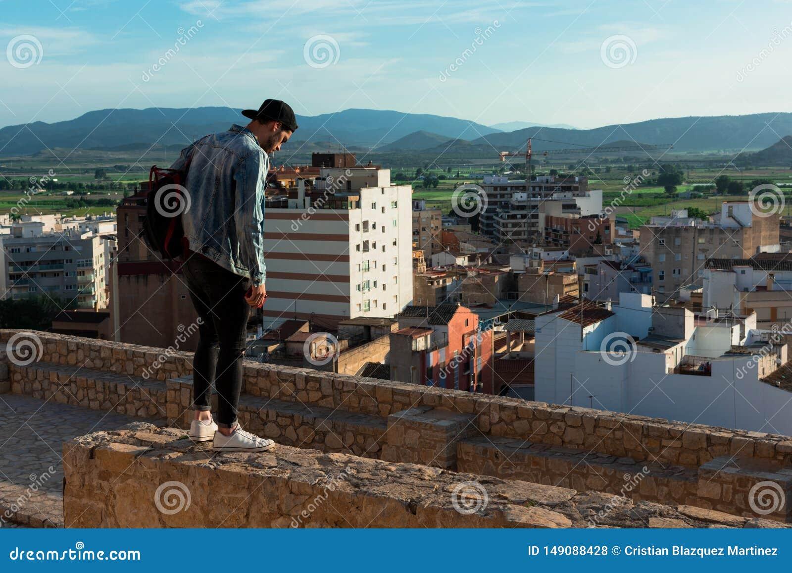 Tillbaka sikt av den unga mannen som ser staden fr?n slotttak