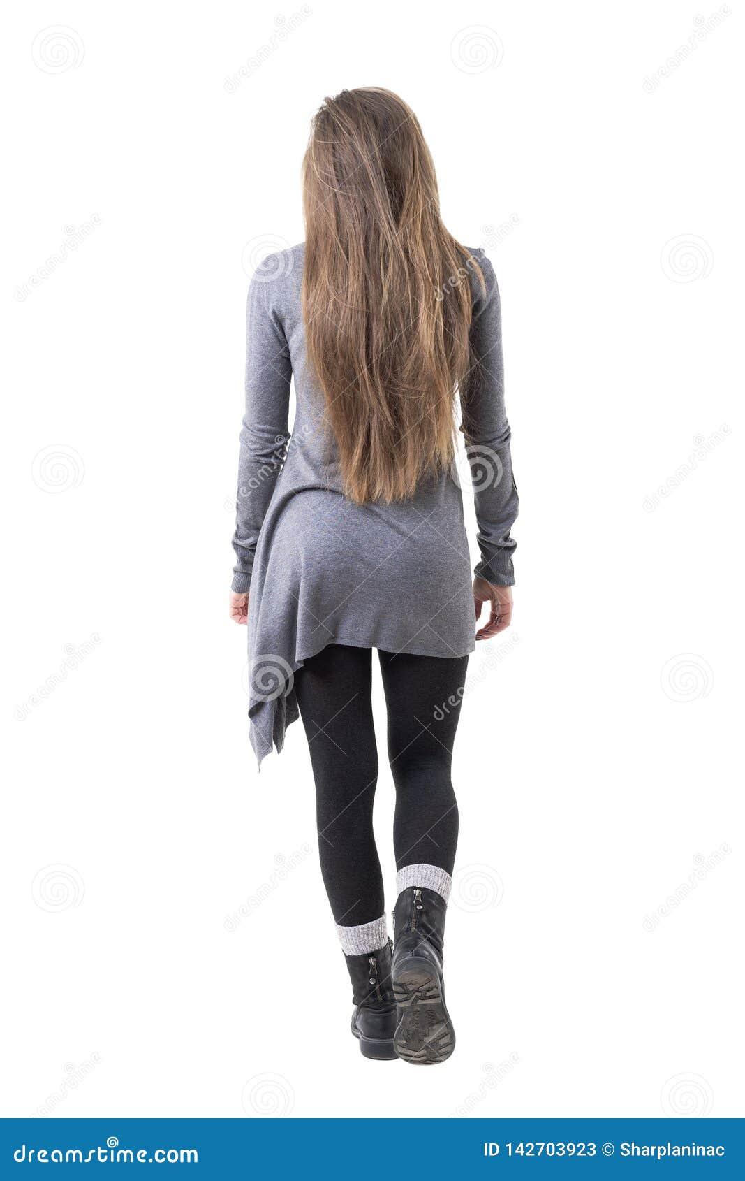 Tillbaka sikt av den unga stilfulla kvinnan med långt sunt hår som bort går