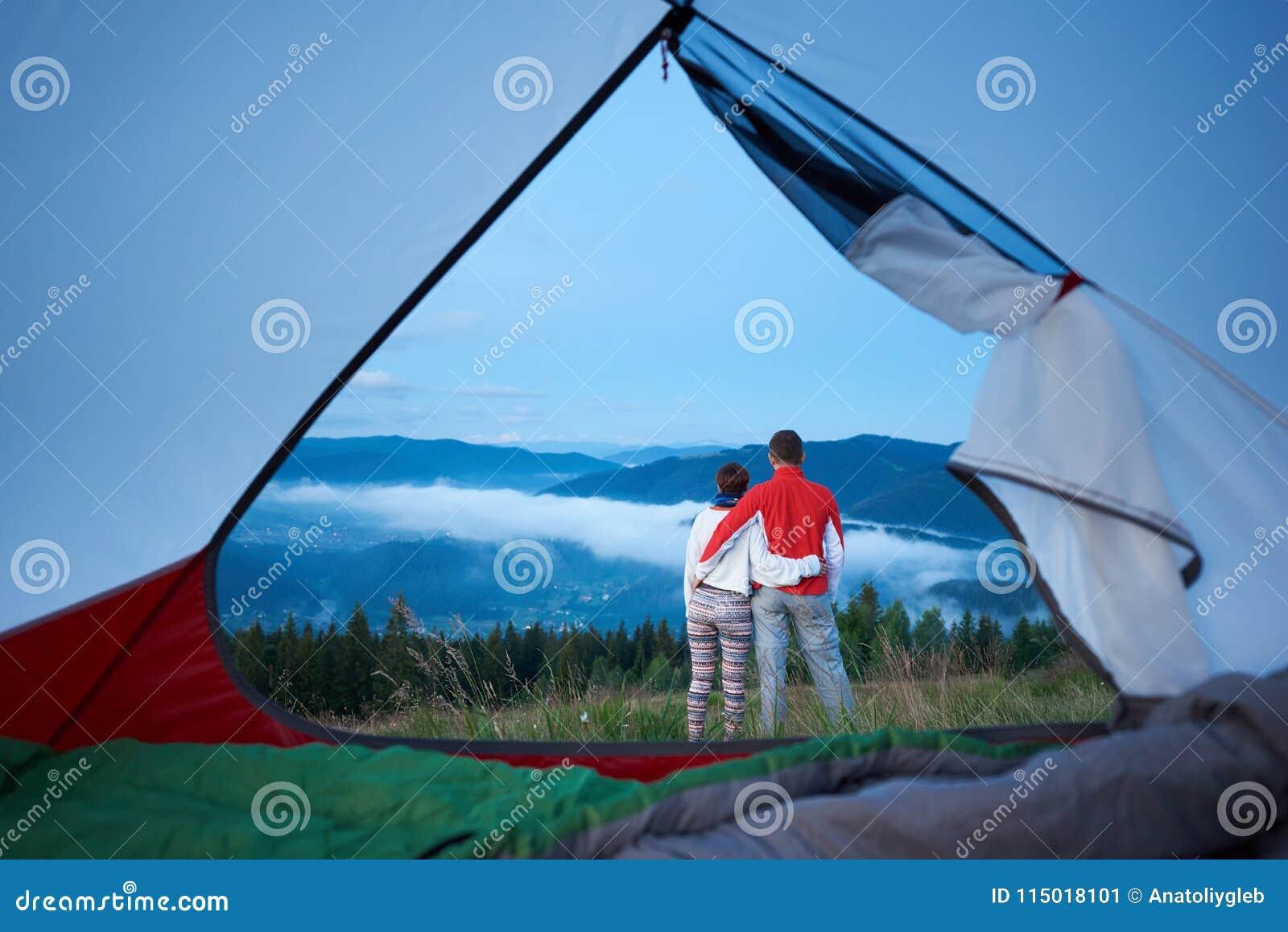 Tillbaka sikt av det söta paranseendet som kramar sig som beundrar sikten av berg