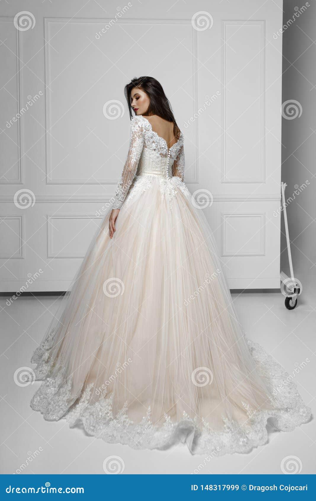 Tillbaka sikt av en modebrunettmodell i härlig lång bröllopsklänning, nära den vita väggen, skott i studion, kopieringsutrymme
