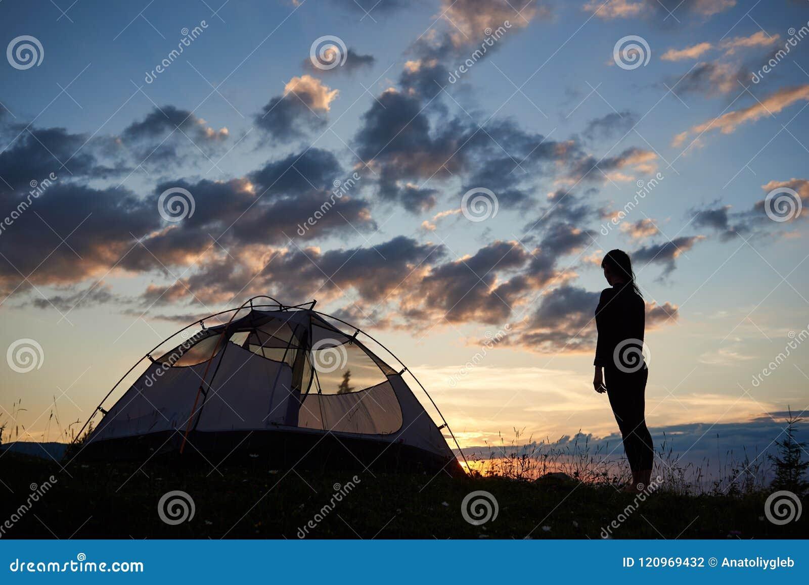Tillbaka sikt av konturflickan som överst står near campa för berg på gräs med vildblommor på gryningen