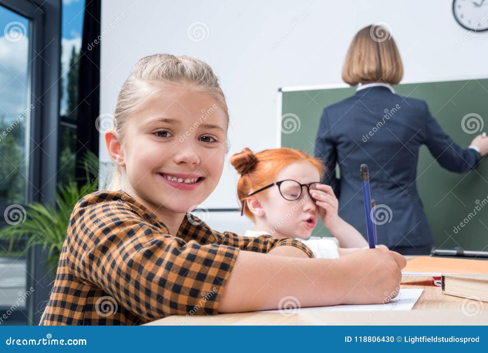 Tillbaka sikt av lärarehandstil på den svart tavlan medan studera för studenter